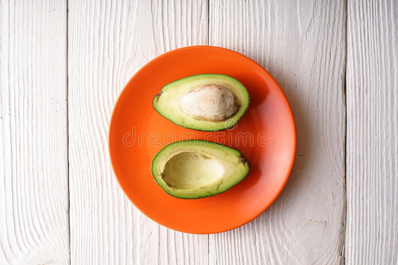 Halves of avocado on the orange plate. Horizontal royalty free stock image