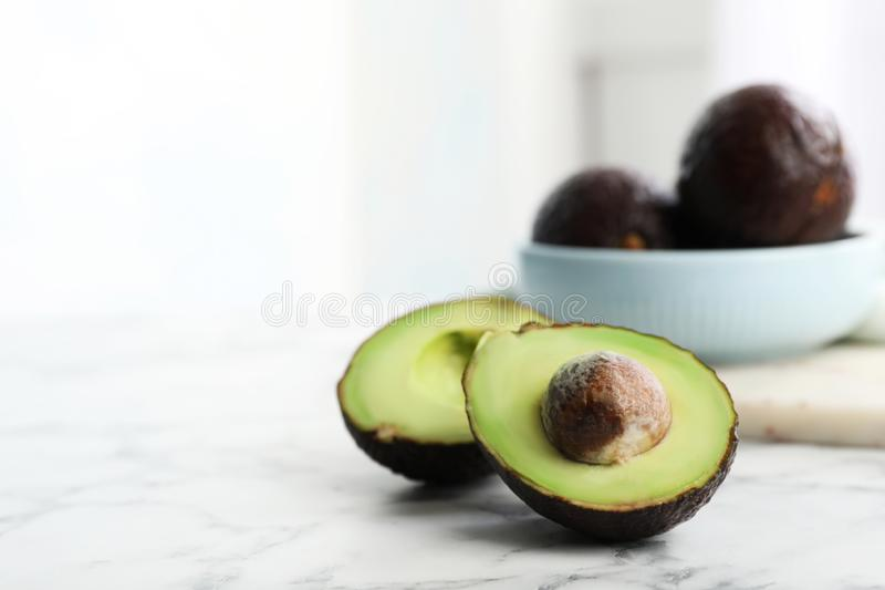 Halves of delicious ripe avocado on white marble table. Against light background stock photos