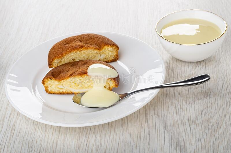 Halves of muffin, spoon with condensed milk, bowl with condensed milk on table royalty free stock photos