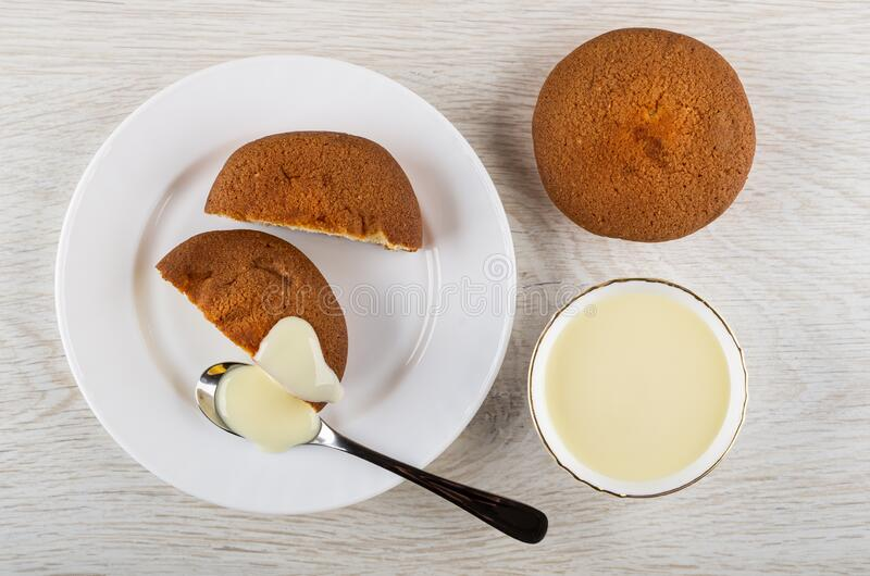 Halves of muffin, spoon with condensed milk, bowl with milk, muffins on table. Top view stock photography