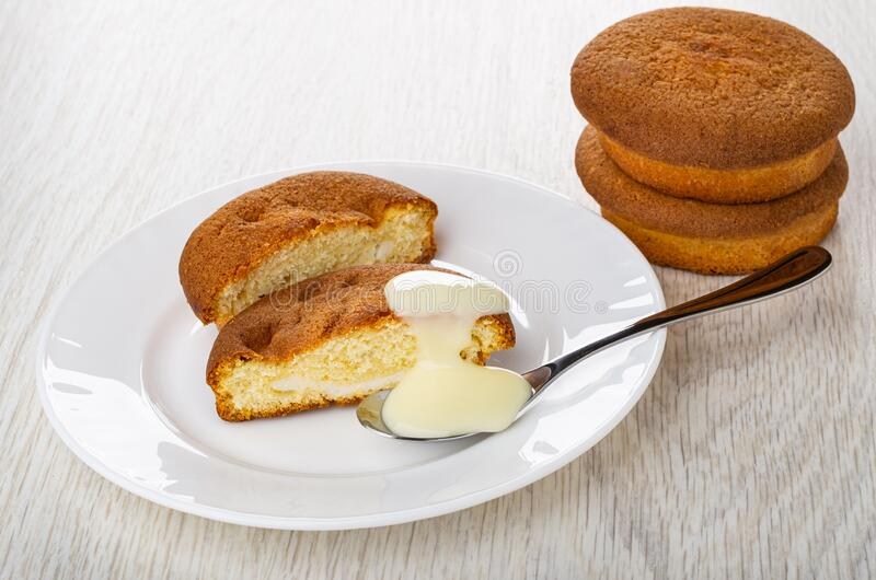 Halves of muffin, spoon with condensed milk, muffins on light wooden table stock photo