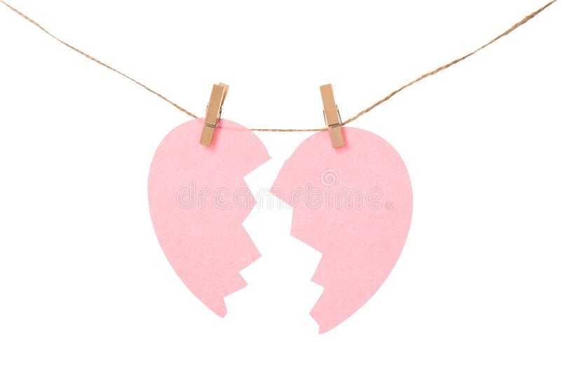 Halves of paper heart hanging on rope against white background. royalty free stock photos