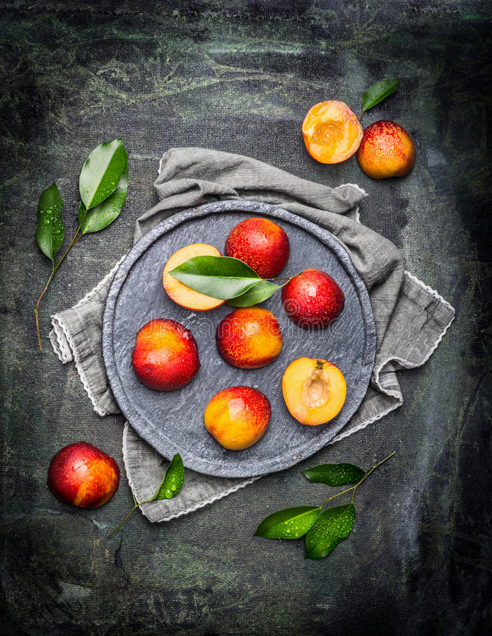 Halves of peaches or nectarines in gray stone plate with leaves. Top view royalty free stock photos