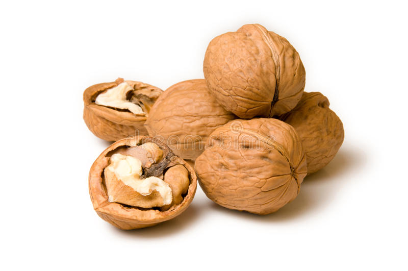 Halves and a pile of walnuts on a white background royalty free stock photo