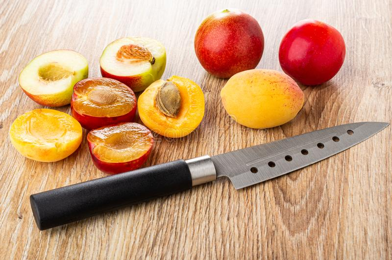 Halves of plum, apricot, nectarine, knife on wooden table. Halves of plum, apricot and nectarine, kitchen knife on wooden table royalty free stock image