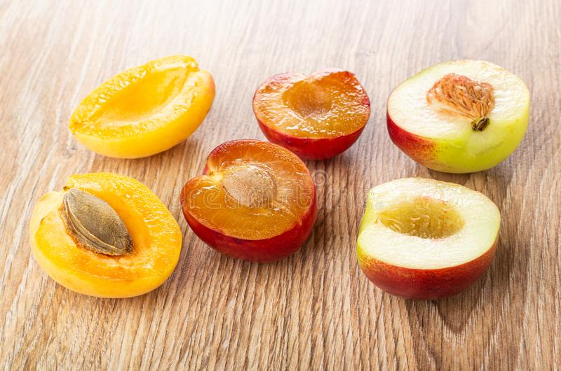 Halves of plum, apricot, nectarine on wooden table. Halves of plum, apricot and nectarine on wooden table stock image