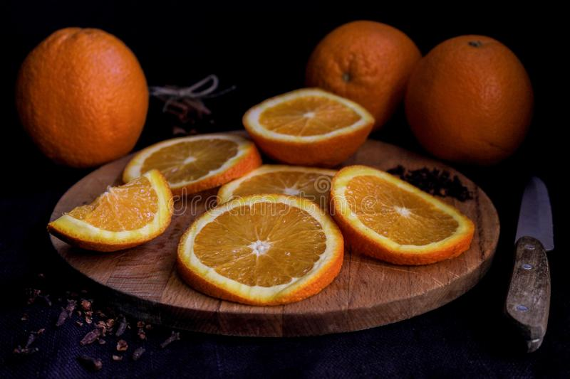 Halves and whole oranges on wooden board over black background, close up royalty free stock photos