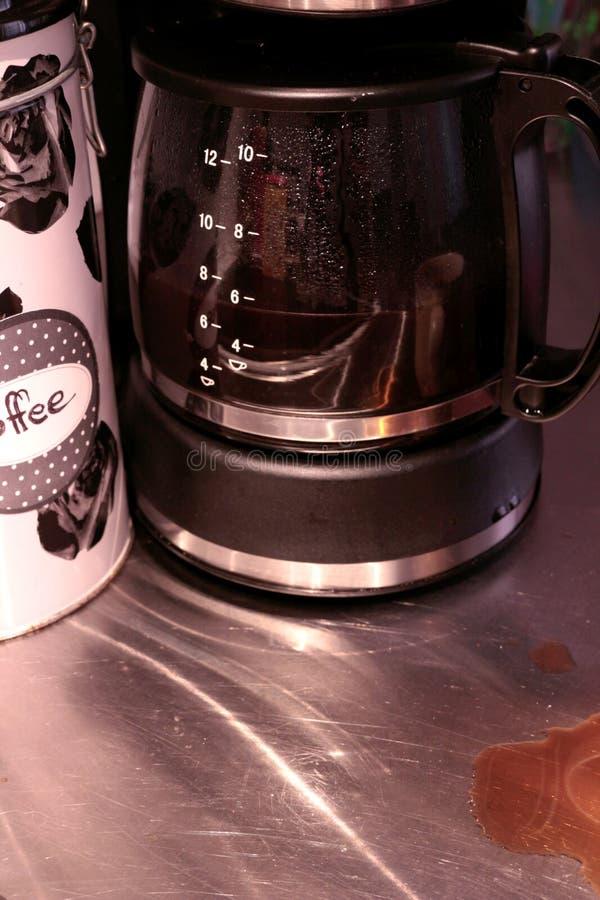 Halvfulla ställningar för en exponeringsglaskaraff nästan i en kaffemaskin Kaffefläckar ses på countertopen arkivfoto