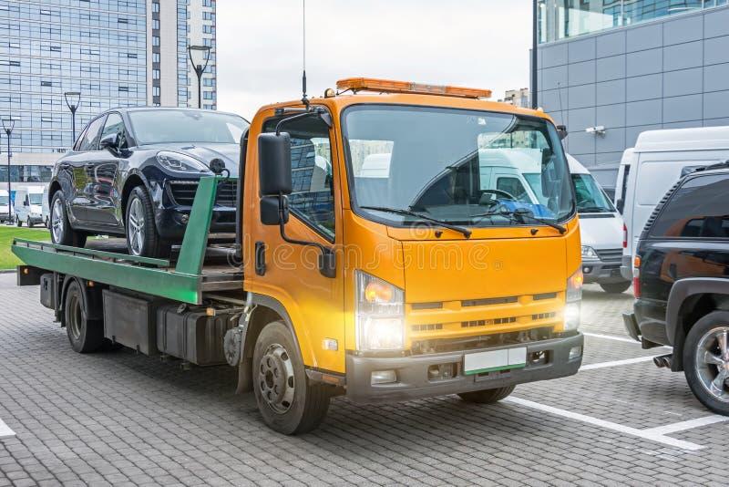 Halvkombibil som laddas på en bärgningsbil som är klar för transport arkivbild