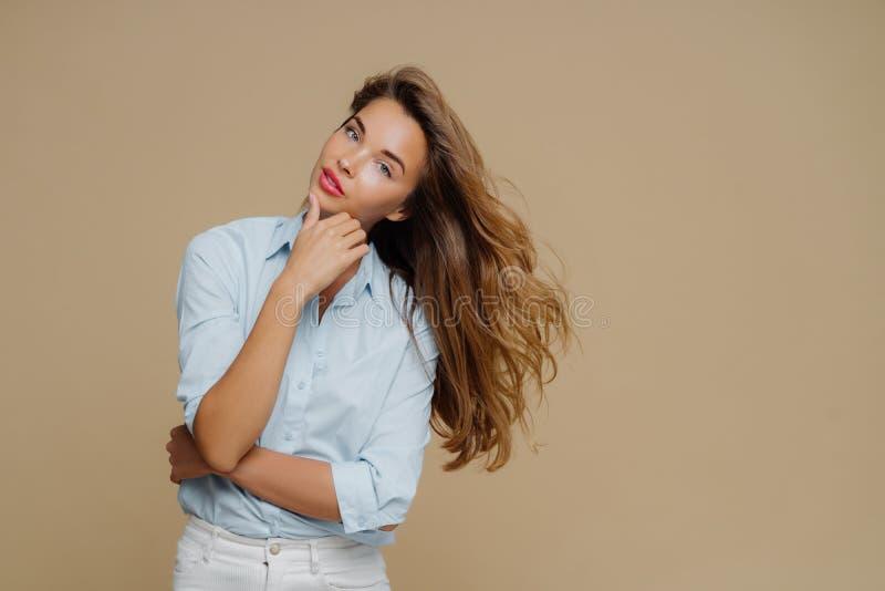 Halvlängdsspruta av attraktiva kvinnliga röra, håller händerna delvis korsade över bröstet, lutar huvudet, har långt rakt hår. arkivfoton