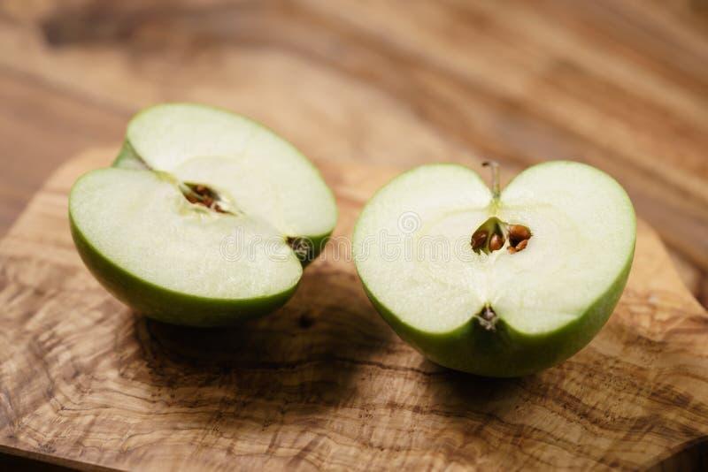 Halvor av det gröna äpplet på den wood tabellen royaltyfri fotografi