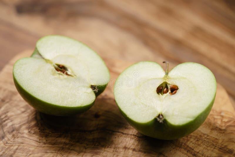 Halvor av det gröna äpplet på den wood tabellen arkivfoton