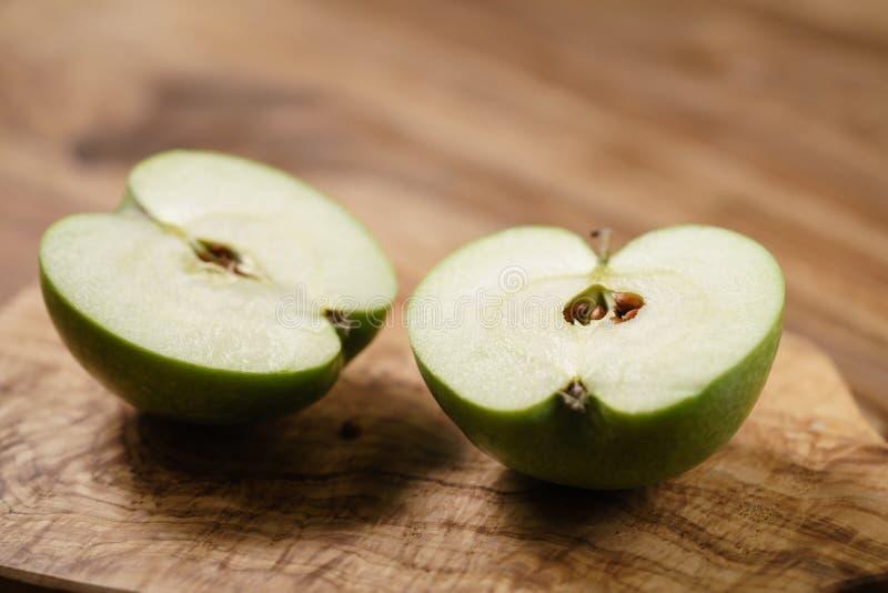 Halvor av det gröna äpplet på den wood tabellen arkivbilder