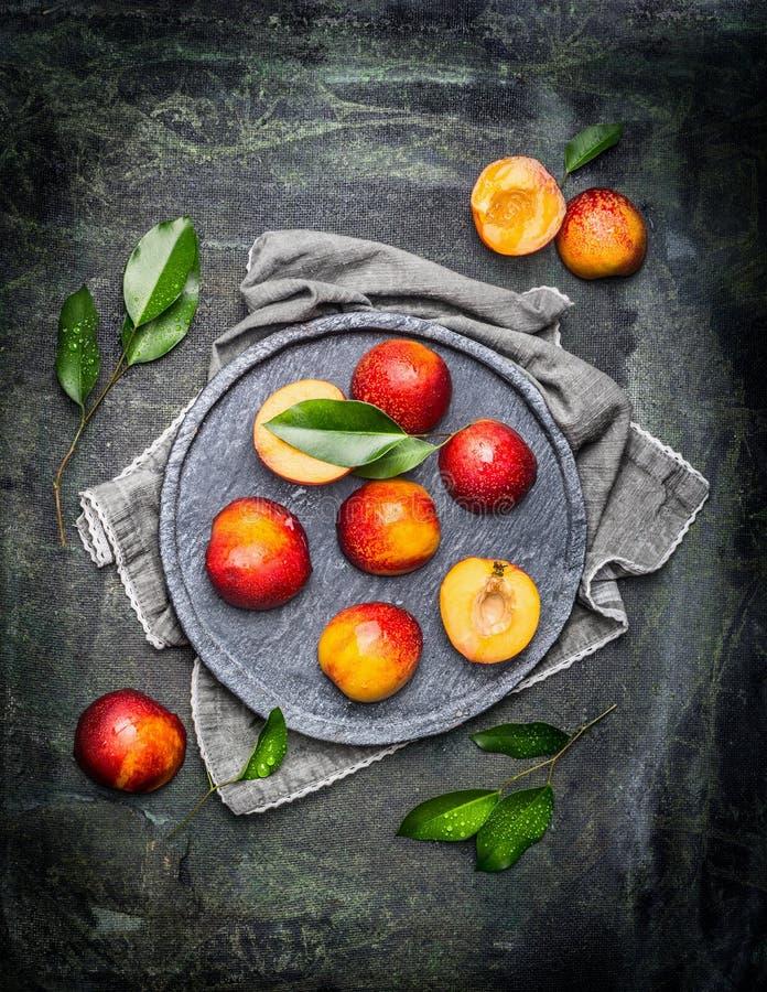 Halvor av persikor eller nektariner i grå färgstenplatta med sidor royaltyfria foton