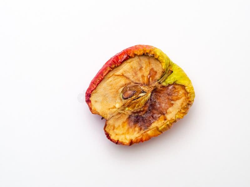 Halvt äpple som rynkas och åldras, torkas - ut och förfallas, sjaskigt och ruttet från över royaltyfri bild