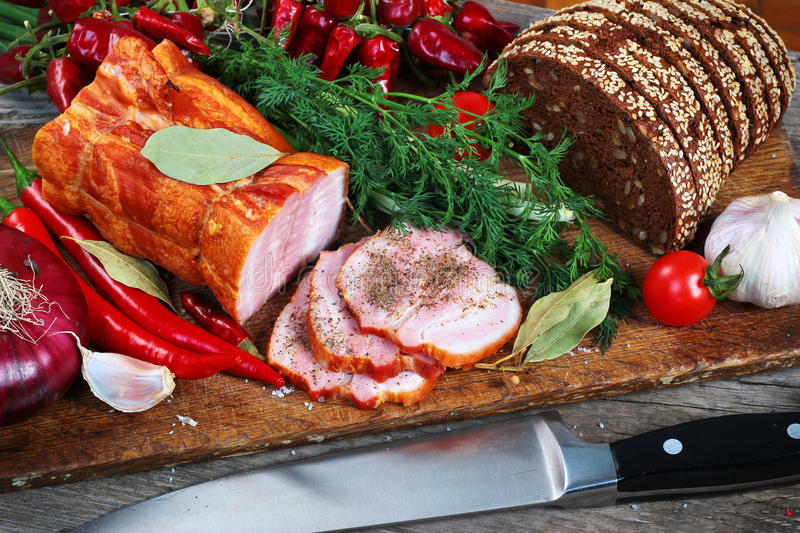 Ham and bread sliced with knife. Green and red vegetables on chopping board.  stock images