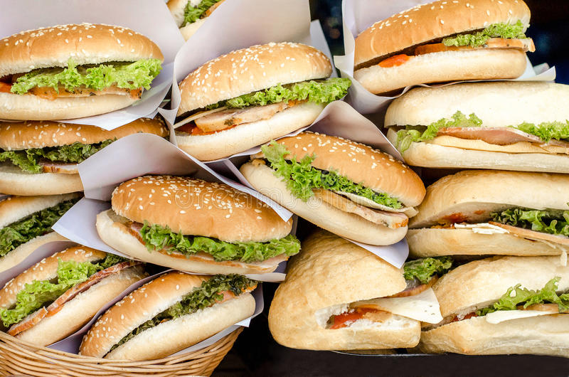 Ham and cheese burgers with greem salad ketchup and sauce lying on a shop window. stock images