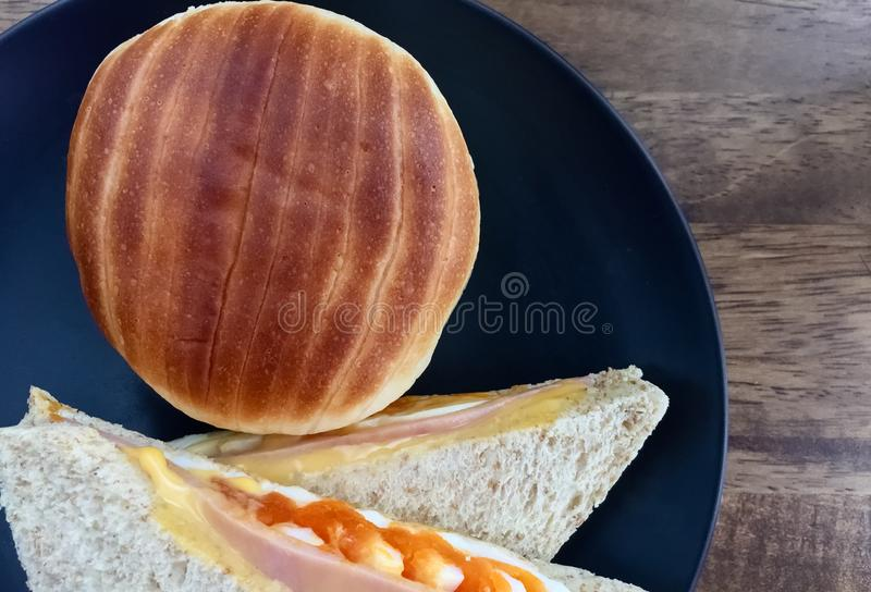 Ham cheese egg sandwich breakfast with brown bread. In a black dish on a table royalty free stock photo