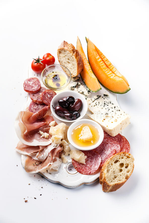 Ham, cheese, melon, olives, bread royalty free stock image