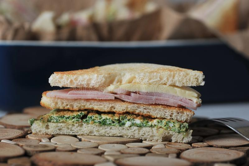 Ham and cheese sandwich on a wooden plate royalty free stock photography