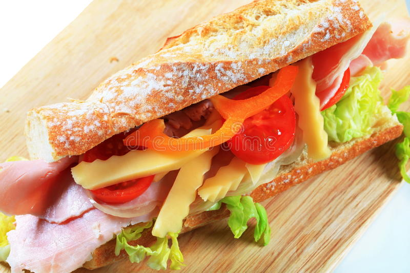 Ham and cheese sub sandwich. On cutting board stock photo