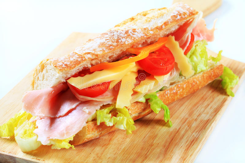 Ham and cheese sub sandwich. On cutting board stock image