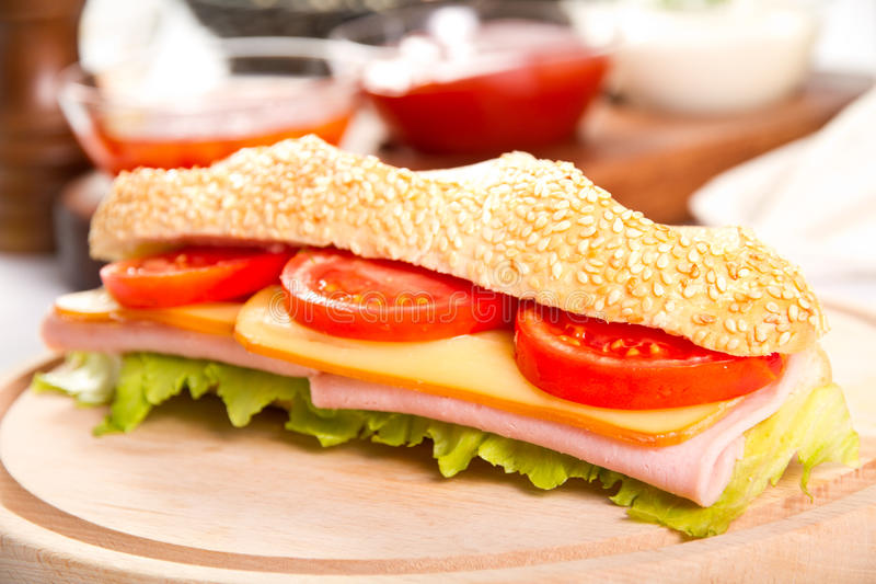 Ham and cheese sub. On a wooden board royalty free stock photo