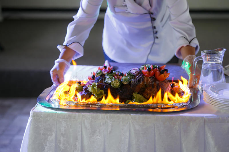 Ham cooking on grill with flames. Dish served with fire chef on background royalty free stock photography