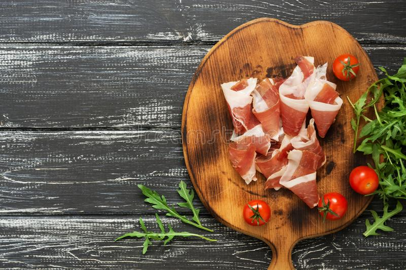 A ham on a cutting board, arugula, cherry tomatoes, a wooden black background. royalty free stock image
