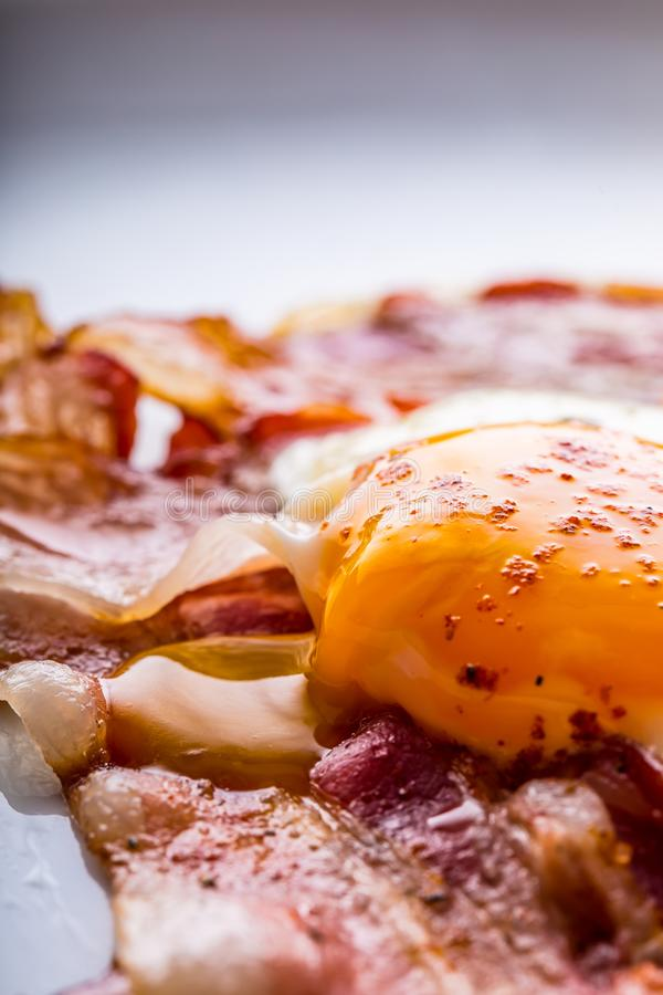 Ham and Eggs. Bacon and Eggs. Salted egg and sprinkled with red pepper. English breakfast.  royalty free stock image