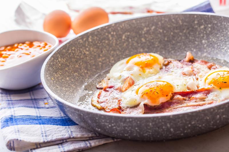 Ham and Eggs. Bacon and Eggs frying on ceramic pan. Salted egg and sprinkled with red pepper. English breakfast.  royalty free stock images