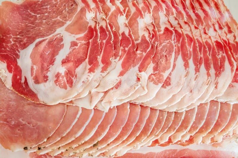 Ham en het aroma van kruiden, dun gesneden betegelde achtergrond Prosciuttoachtergrond Sluit omhoog royalty-vrije stock foto