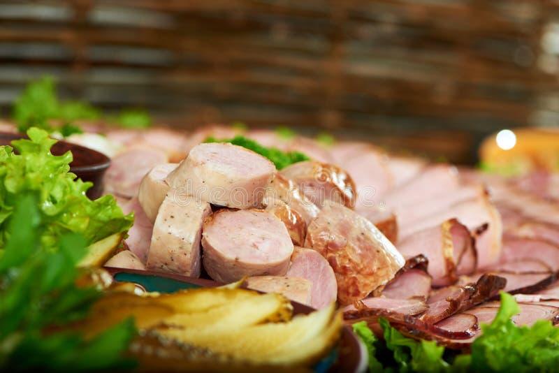 Ham en worstreeks met slabladeren dat wordt verfraaid stock afbeeldingen