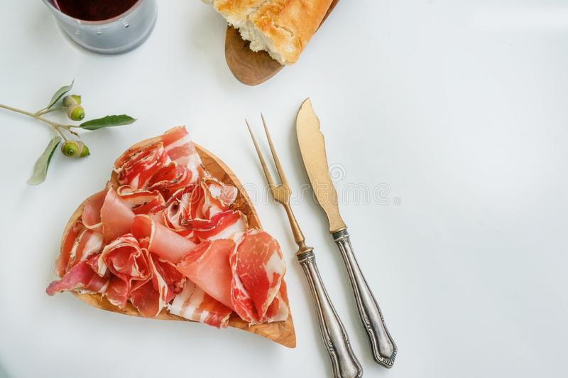 Ham and flavor spices, thinly sliced on a white table with bread. close up. Copy space.  royalty free stock photography