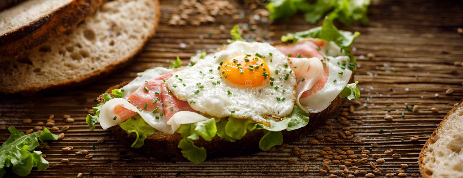 Ham and fried egg open sandwich, Sourdough bread sandwich with lettuce, ham and fried egg on a rustic wooden table royalty free stock photography