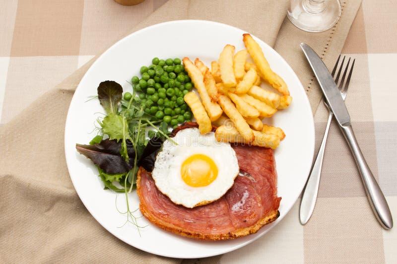 Ham-lapje vlees met een gebraden ei stock afbeelding