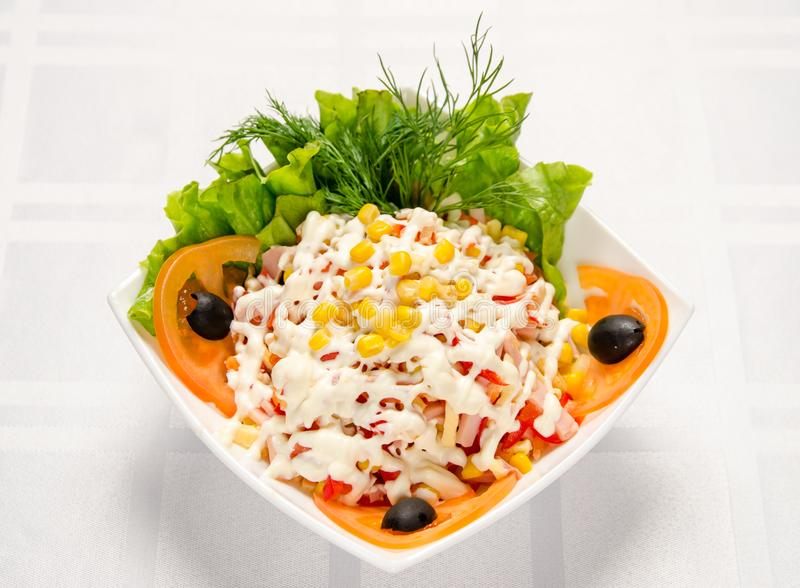 Ham salad with corn, cheese, tomatoes, Bulgarian pepper, lettuce, green, olive and mayonnaise royalty free stock image