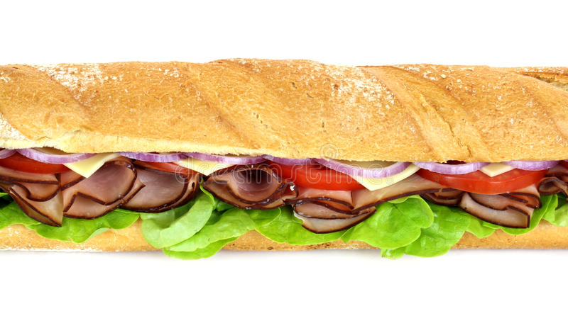 Ham And Salad Sub. Giant ham, tomato, lettuce, cheese and onion sub ready to serve royalty free stock image