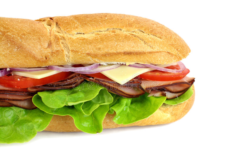 Ham And Salad Sub. Giant ham, tomato, lettuce, cheese and onion sub ready to serve royalty free stock photo