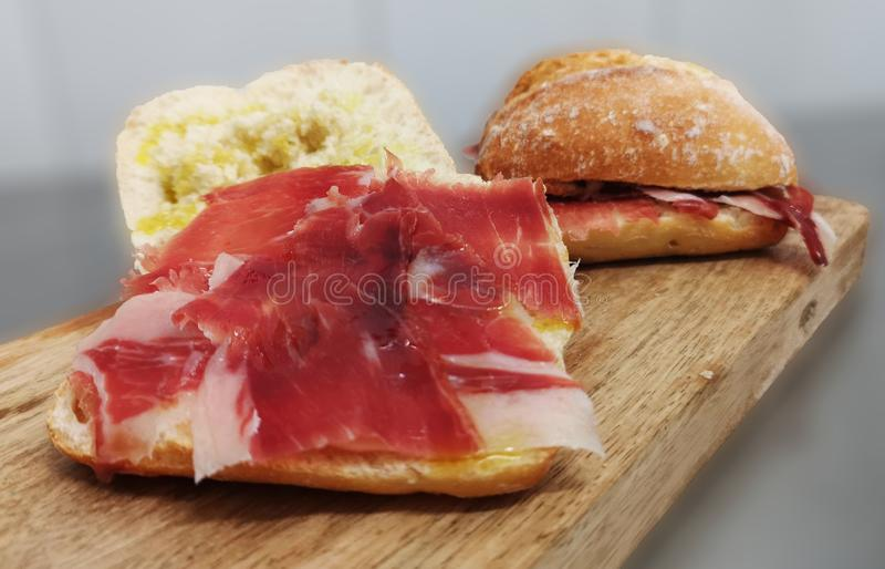 Ham sandwich iberico pata negra. Two sandwich spanish ham bellota. Appetizing deli on wooden table. Delicious appetizer gourmet pata negra royalty free stock image