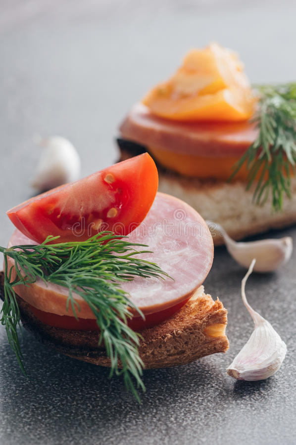 A ham sandwich with red and yellow tomatoes on a gray surface. royalty free stock photography
