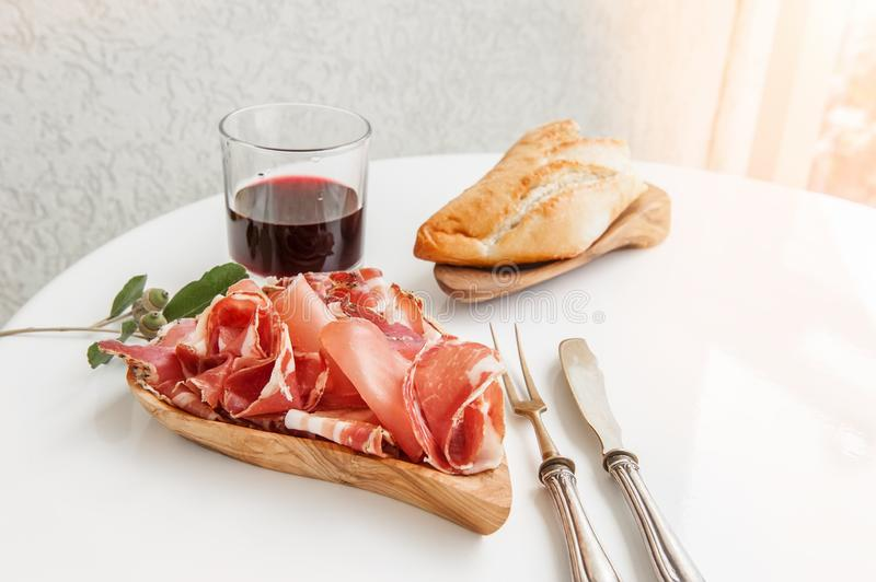 Ham in spices, thinly sliced on a white table with bread and antique Cutlery. Copy space stock photo