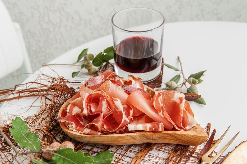 Ham in spices, thinly sliced on a white table with bread and antique Cutlery.  royalty free stock image