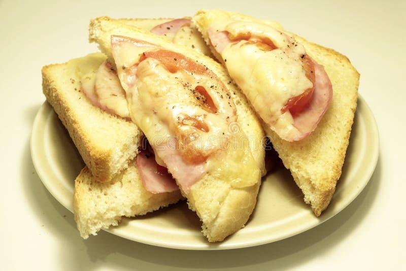 Ham, tomaten en de driehoeken van de kaastoost die op een plaat wordt gediend royalty-vrije stock afbeeldingen