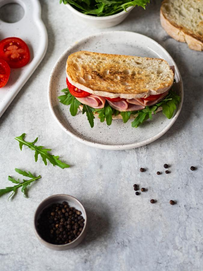 Ham, tomato and arugula sandwich on toasted bread slices on a white plate and other ingredients on a gray background royalty free stock image