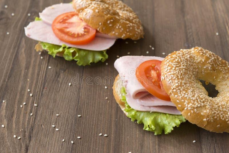 Ham , tomato, green lettuce leaf on round sesame bun, 2 sandwiches on wooden background royalty free stock photo