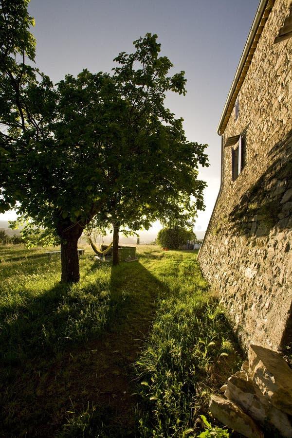 Hamaca en los árboles y el cortijo de piedra viejo Francia fotos de archivo