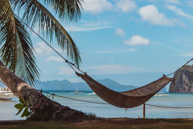 Hamaca vacía con la palmera y el barco en la playa tropical Paisaje del centro turístico de Filipinas Concepto idílico de las vac fotos de archivo libres de regalías