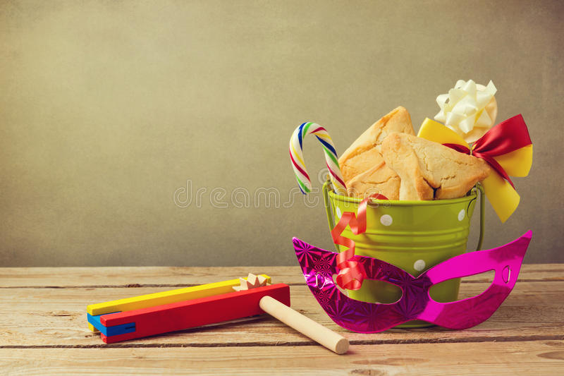 Hamantaschen cookies in bucket with grogger noise maker and carnival mask. Gift for purim festival royalty free stock photo
