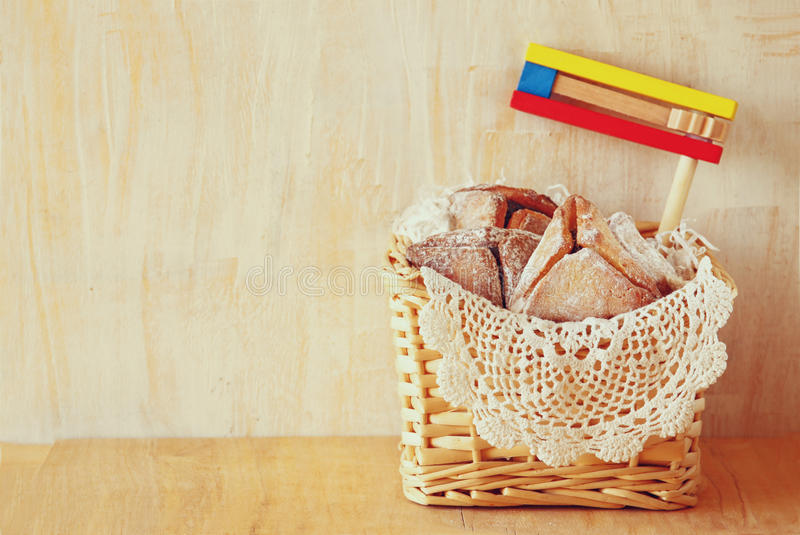 Hamantaschen cookies or hamans ears and noisemaker for Purim celebration (jewish holiday).  royalty free stock photo